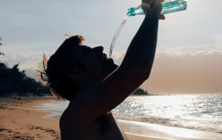 Ein Mann der in der Hitze Wasser trinkt